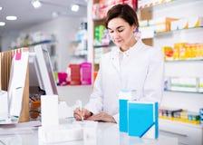 Farmacêutico fêmea que verifica a variedade das drogas na farmácia fotos de stock