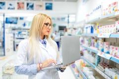 Farmacêutico louro no campo médico usando a tecnologia do portátil e da tabuleta para afixar anúncios em linha da droga Fotografia de Stock