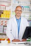 Farmacêutico maduro seguro Standing At Counter Fotografia de Stock