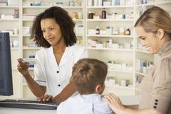Farmacêutico na farmácia com mãe e criança imagem de stock royalty free