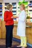 Farmacêutico que dá a ordem da medicamentação do cliente fotografia de stock royalty free
