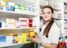 Farmacêutico que guarda para fora tabuletas na garrafa no drugst Fotografia de Stock Royalty Free