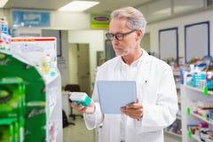 Farmacêutico que guarda a tabuleta e que olha a medicina fotografia de stock