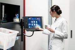 Farmacêutico que usa um computador ao controlar o estoque da droga imagem de stock