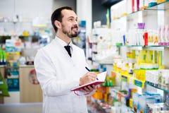 Farmacêutico que verifica drogas na farmácia fotografia de stock