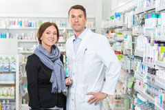Farmacêutico seguro Standing With Customer dentro Imagens de Stock