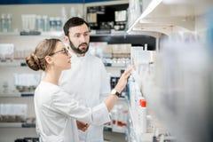 Farmacêuticos que trabalham na loja da farmácia imagem de stock royalty free