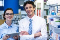 Farmacêuticos que usam a tabuleta digital na farmácia fotos de stock