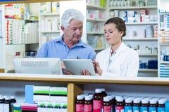 Farmacêuticos que usam a tabuleta digital no contador fotografia de stock royalty free