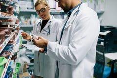 Farmacêuticos que verificam o inventário na farmácia fotografia de stock royalty free