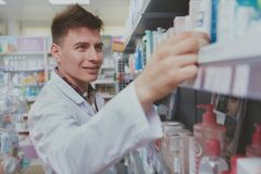 Farmac?utico masculino consider?vel que trabalha em sua drograria imagem de stock royalty free