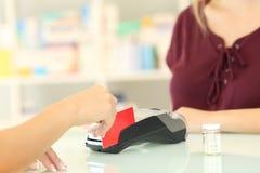 Farmaceuta ładuje z kredytową kartą w aptece obrazy royalty free