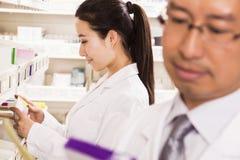 Farmaceuta bierze w dół i egzamininuje recepturowego lekarstwo w aptece Zdjęcia Stock