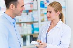 Farmaceuta i klient przy apteką obrazy stock
