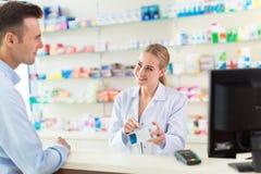 Farmaceuta i klient przy apteką obraz royalty free