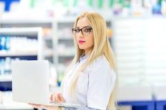 Farmaceuta naukowiec używa nowożytną technologię w aptece Farmaceuty sprzedawania antybiotyki w aptece zdjęcie royalty free
