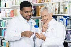 Farmaceuta Patrzeje szampon butelkę W aptece Zdjęcia Stock