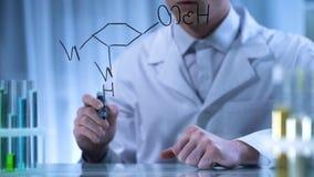 Farmaceuta pisze formalnie chemicznej formule na przejrzystej desce, badanie obraz stock
