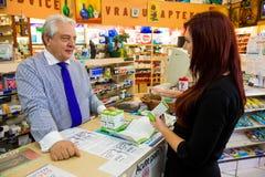 Farmaceuta pomaga klienta w detalicznym apteka sklepie fotografia stock