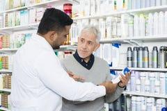 Farmaceuta Pomaga Starszego klienta W kupienie produkcie zdjęcia royalty free