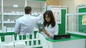Farmaceuta pracuje z pastylką w aptece trzyma je w jej ręce podczas gdy czytający informację Obrazy Royalty Free