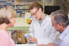 Farmaceuta trzyma butelkę leki opowiada klient zdjęcia stock