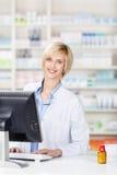 Farmaceuta Używa komputer Przy apteka kontuarem fotografia royalty free
