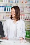 Farmaceuta Używa komputer Przy De Podczas gdy Trzymający recepta papier zdjęcia stock