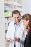 Farmaceuta wyjaśnia coś pacjent Zdjęcia Royalty Free