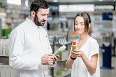 Farmaceuta z klientem przy apteka sklepem Zdjęcia Stock