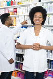 Farmaceuta Z rękami Spinał Uśmiecha się Podczas gdy kolegi ułożenie Zdjęcia Stock