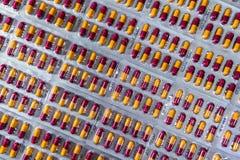 Farmaceutisk bransch Röd-guling kapselpiller i blåsapacke Farmaceutiskt f?rpacka Apotekprodukt global sjukv?rd fotografering för bildbyråer