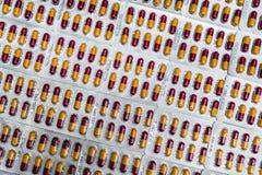 Farmaceutisk bransch R?d-guling kapselpiller i bl?sapacke Farmaceutiskt f?rpacka Apotekprodukt global sjukv?rd royaltyfri fotografi