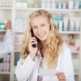 Farmaceuty mienia recepty papier Podczas gdy Używać Cordless telefon Zdjęcia Royalty Free