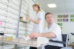 Farmaceuty pozycja i apteka technik w wózku inwalidzkim Zdjęcia Stock