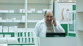 Farmaceuty rozmowa z klientem używa telefon komórkowego w aptece Obrazy Stock