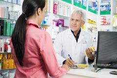 Farmaceuty Writing Na schowku Podczas gdy Patrzejący kobiety Obrazy Stock