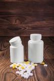 Farmaceutyczne medycyn pigułki, pastylki i kapsuły na drewnianym tle, Dwa medycyny matt biała butelka z lekami obraz royalty free