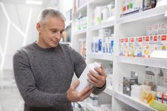 Farmaci maturi di acquisto dell'uomo alla farmacia fotografia stock