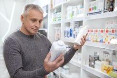 Farmaci maturi di acquisto dell'uomo alla farmacia immagini stock