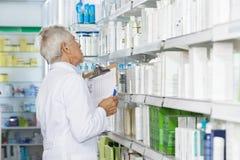 Farmacia masculina de Counting Stock In del químico Foto de archivo libre de regalías