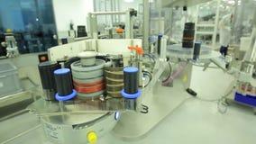 farmacie De farmaceutische arbeider stelt de verpakkende machine van de tabletblaar in werking vervaardiging van spuiten Spuit stock footage