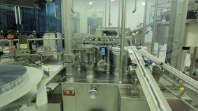 farmacie De farmaceutische arbeider stelt de verpakkende machine van de tabletblaar in werking vervaardiging van spuiten Spuit stock videobeelden