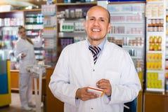 Farmacista adulto che sta allo scrittorio di paga Fotografie Stock Libere da Diritti