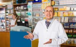 Farmacista allegro che sta allo scrittorio di paga Immagine Stock Libera da Diritti
