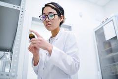 Farmacista asiatico che controlla l'etichetta della pillola immagine stock
