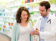 Farmacista attraente che consiglia un paziente Fotografia Stock