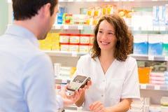 Farmacista attraente che prende la carta di assicurazione del healt Immagine Stock