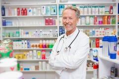 Farmacista in cappotto del laboratorio con lo stetoscopio e armi attraversate Fotografia Stock