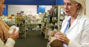 Farmacista che assiste il pacchetto della droga al cliente video d archivio